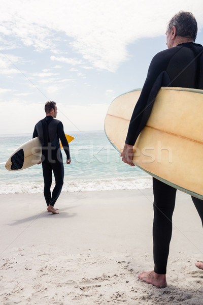 Hombres caminando playa tabla de surf Foto stock © wavebreak_media
