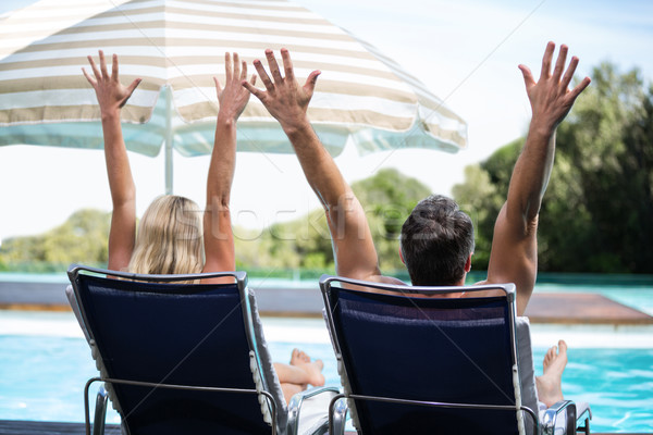 Rear view of couple relaxing on sun lounger with hand raised Stock photo © wavebreak_media