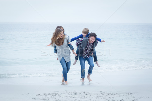 Parents running while carrying children at sea shore  Stock photo © wavebreak_media