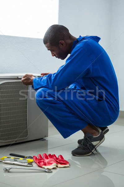 Handyman testing air conditioner with screwdrive Stock photo © wavebreak_media