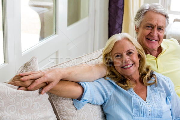 Romantic senior couple sitting in living room at home Stock photo © wavebreak_media