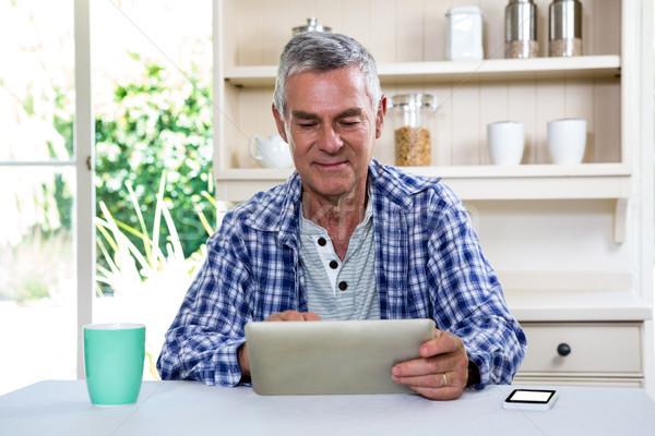 Starszy człowiek cyfrowe tabletka półki kuchnia Zdjęcia stock © wavebreak_media