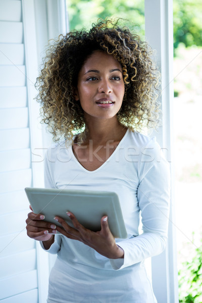 Thoughtful woman standing near the window and using a digital ta Stock photo © wavebreak_media