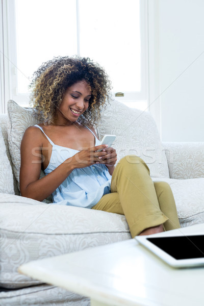 Young woman sitting on sofa and text messaging on phone Stock photo © wavebreak_media