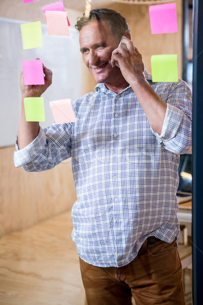 Man writing on sticky notes while talking on phone Stock photo © wavebreak_media