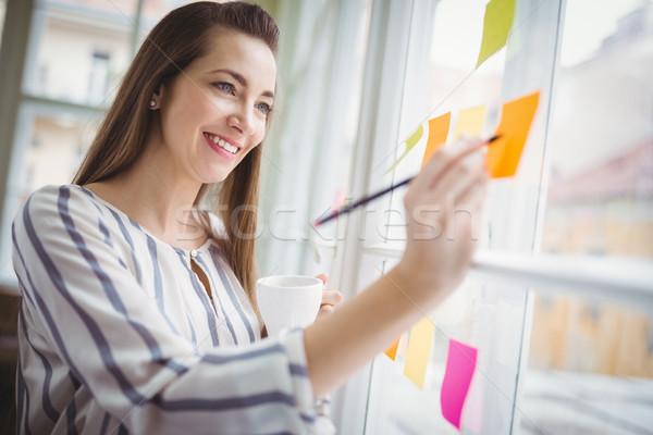 Kobieta interesu piśmie przyczepny zauważa twórczej biuro Zdjęcia stock © wavebreak_media