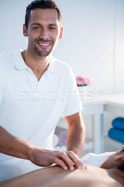 Smiling physiotherapist giving back massage to a woman Stock photo © wavebreak_media