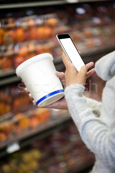 Nő mobiltelefon vásárlás élelmiszer középső rész áruház Stock fotó © wavebreak_media