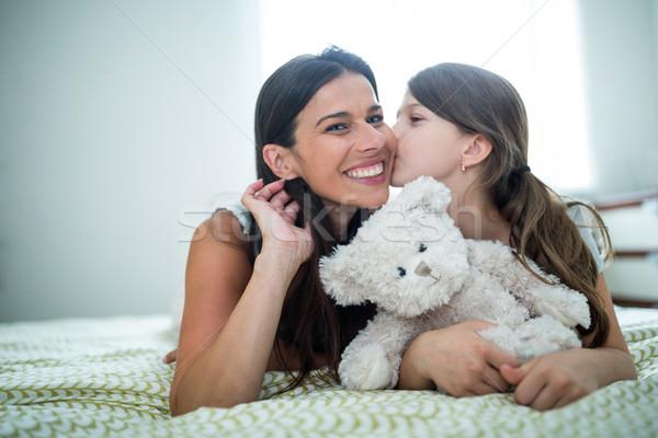 Filha beijando mãe bochechas cama casa Foto stock © wavebreak_media