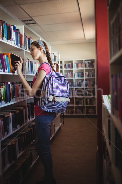 Schoolgirl selecting book in library Stock photo © wavebreak_media