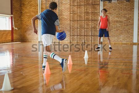 High school boys practicing football using cones for dribbling drill in the court Stock photo © wavebreak_media