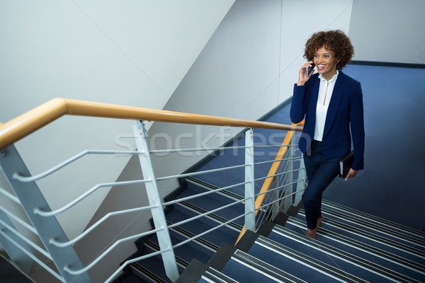 Businesswoman talking on mobile phone while climbing steps Stock photo © wavebreak_media