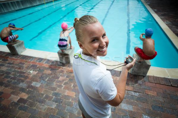 Cheerful Instructor monitoring children at poolside Stock photo © wavebreak_media