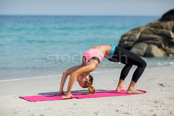 Side view of young woman exercising on exercise mat at beach Stock photo © wavebreak_media