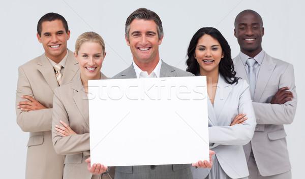 Business team holding a white card Stock photo © wavebreak_media
