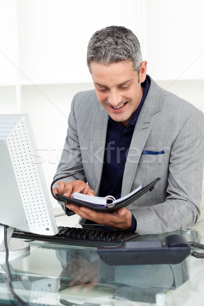 Smiling businessman consulting his agenda Stock photo © wavebreak_media