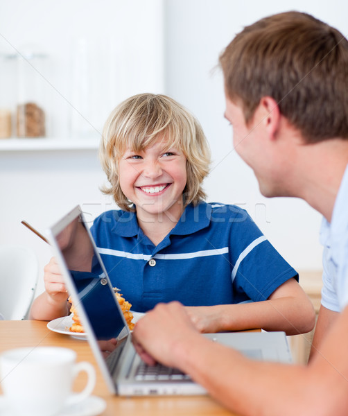 Smiling boy having breakfast while his father using a laptop Stock photo © wavebreak_media