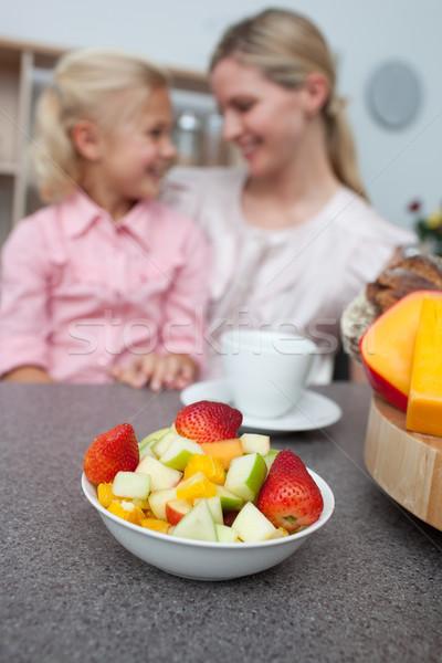 Blond little girl eating strawberry with her mother  Stock photo © wavebreak_media