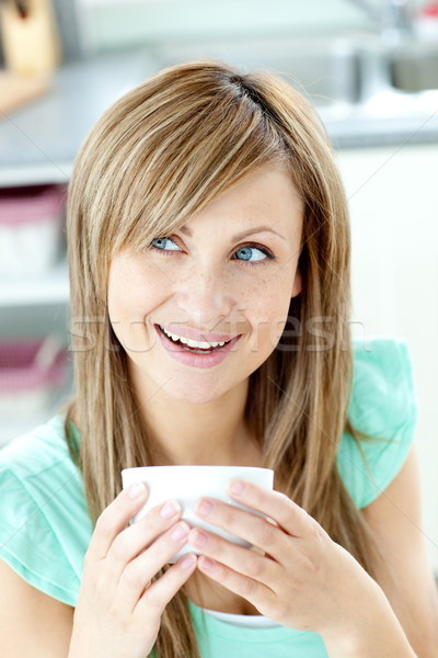 Portrait of a woman holding a cup of tea in the kitchen Stock photo © wavebreak_media