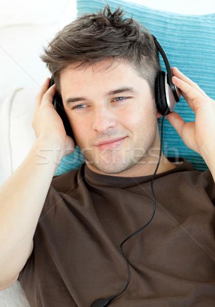 Bell'uomo cuffie ascoltare musica soggiorno rock divertimento Foto d'archivio © wavebreak_media