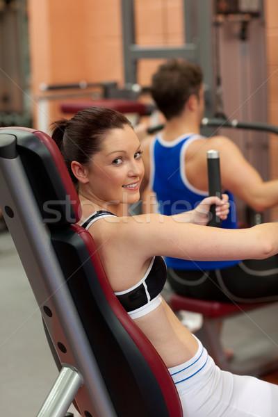 Pretty athletic woman using a shoulder press Stock photo © wavebreak_media