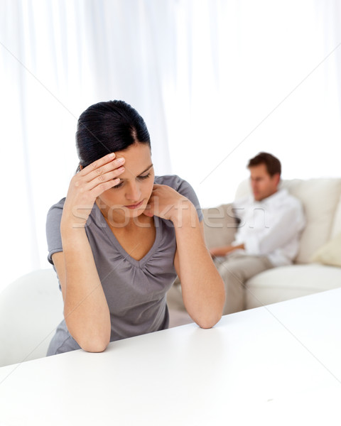 Stock photo: Worried woman sitting at a table while her boyfriend is lying on the sofa in the background