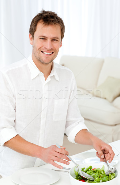 Joyful man serving salad standing at a table in the living room at home Stock photo © wavebreak_media