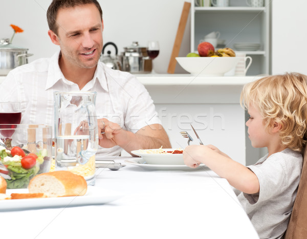 Happy dad looking at his son eating pasta in the kitchen  Stock photo © wavebreak_media