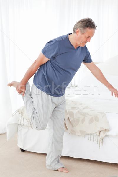 Mature man stretching in his bedroom Stock photo © wavebreak_media