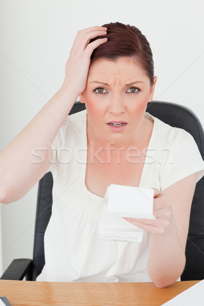 Young attractive red-haired female being scared by the amount of the receipt while sitting at a desk Stock photo © wavebreak_media