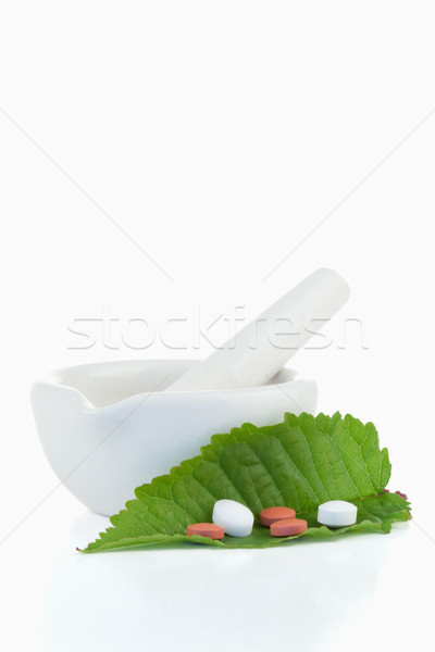 Mortar and pestle with pills on a leaf against a white background Stock photo © wavebreak_media