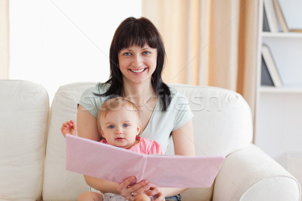 Good looking woman holding her baby and a book in her arms while sitting on a sofa in the living roo Stock photo © wavebreak_media