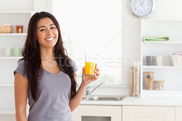 Stock photo: Attractive woman holding a glass of orange juice while standing in the kitchen