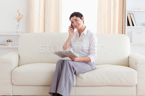 Beautiful Woman with a cellphone and a newspaper looking at the camera in the living room Stock photo © wavebreak_media