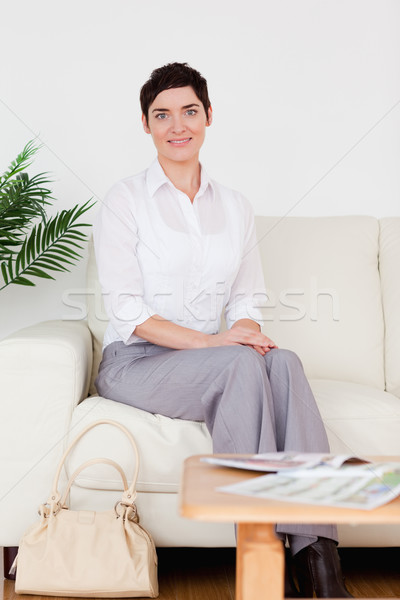 Cute short-haired woman sitting on a sofa in a waiting room Stock photo © wavebreak_media