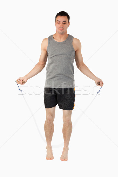 Young sportsman rope jumping against a white background Stock photo © wavebreak_media