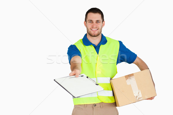 Smiling young delivery man with parcel asking for signature against a white background Stock photo © wavebreak_media