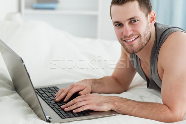 Bell'uomo utilizzando il computer portatile pancia camera da letto computer felice Foto d'archivio © wavebreak_media