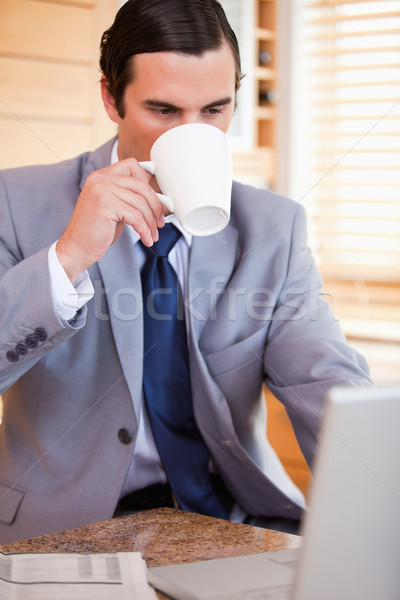 Young businessman taking a sip of coffee next to his laptop Stock photo © wavebreak_media