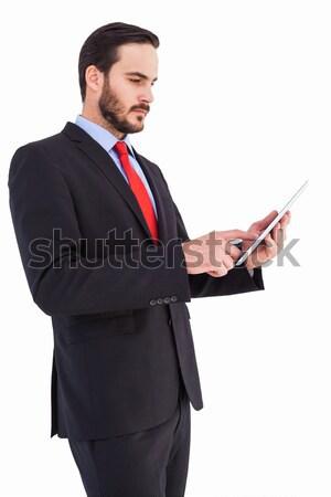 Smiling businessman sending a text message against a white background Stock photo © wavebreak_media