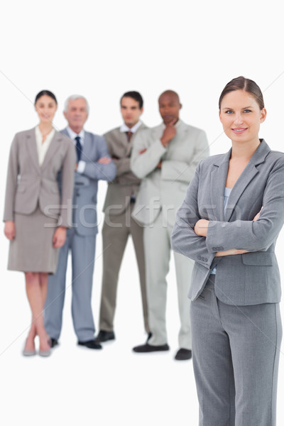 Stock photo: Saleswoman with arms folded and her team behind her against a white background