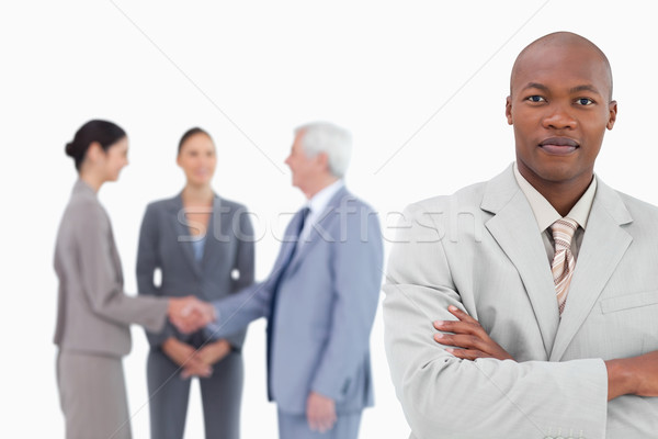 Businessman with arms folded and trading partners behind him against a white background Stock photo © wavebreak_media