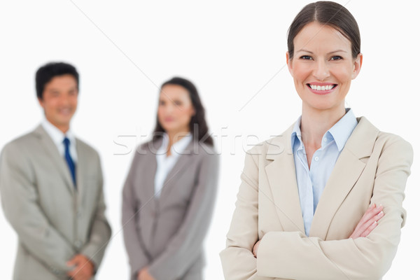 Smiling saleswoman with arms folded and associates behind her against a white background Stock photo © wavebreak_media