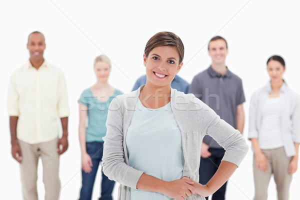 Close-up of a woman smiling with her hands on her hips with people behind against white background Stock photo © wavebreak_media