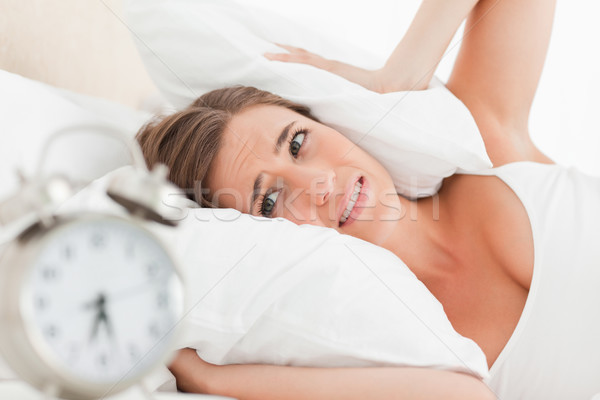 A woman uses a pillow to cover her ears as her alarm clock rings loudly. Stock photo © wavebreak_media