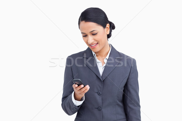 Close up of smiling saleswoman reading text message against a white background Stock photo © wavebreak_media