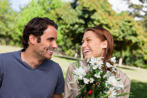Man smiling as he watches his friend laughing while holding a bunch of flowers while sitting in a br Stock photo © wavebreak_media