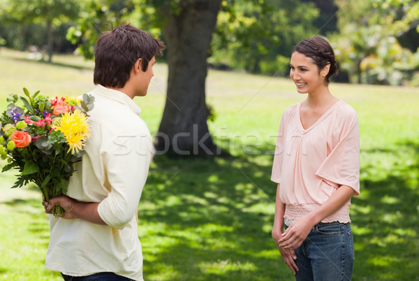 Woman smiling as she greets her friend who is holding flowers behind his back Stock photo © wavebreak_media