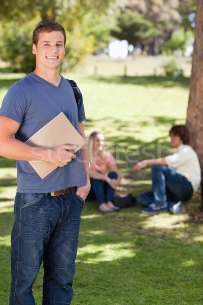 Student smiling while holding a textbook in a park with friends in background Stock photo © wavebreak_media