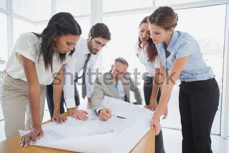 Stock photo: Young executive explaining an idea to his colleagues using flipchart sheets